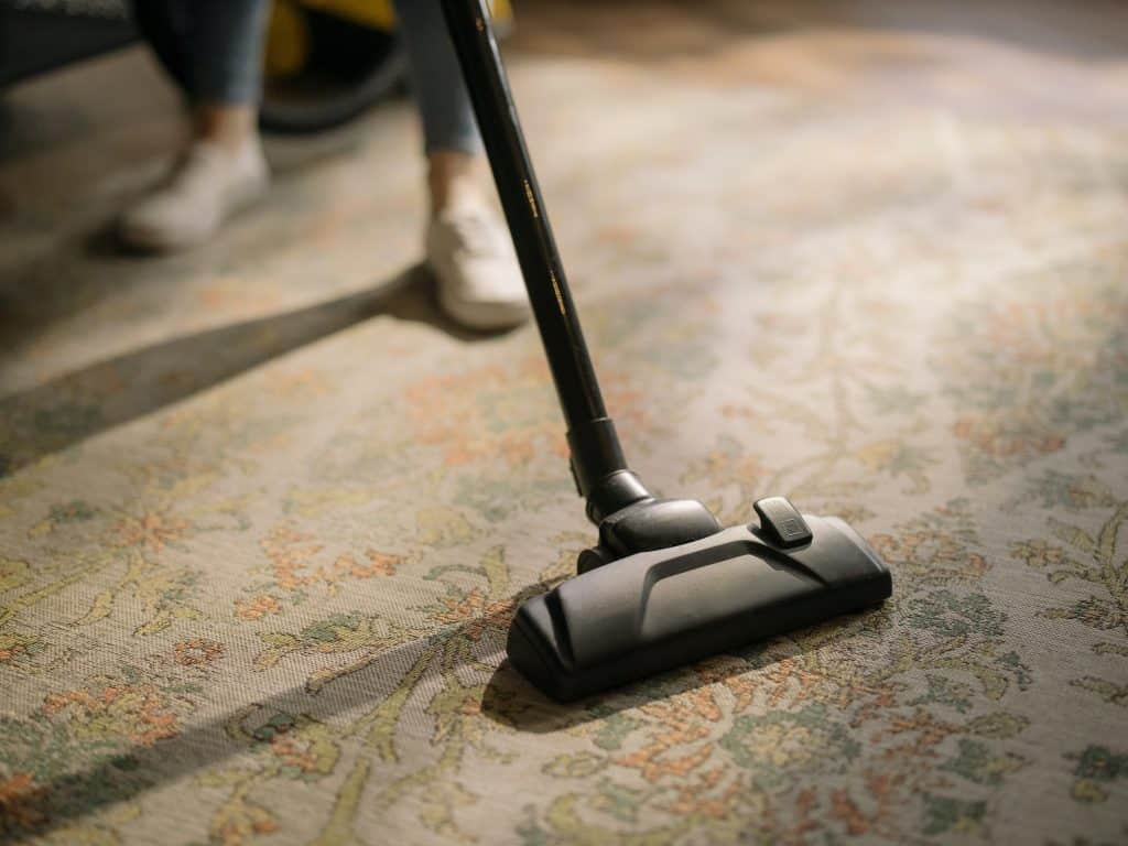 A person cleaning a brown carpet with a carpet cleaner vacuum