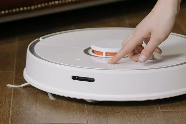 White Roomba cleaning the floor